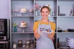 Happy beaming confectioner feeling proud of her perfect chocolates. Proud confectioner. Happy beaming confectioner wearing striped apron feeling proud of her royalty free stock photos