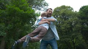 Happy beard father hugging and whirling his son. Dad meets his son from elementary school. the end of the school day. Concept stock video