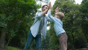 Happy beard father and son. having fun and jumping raising their hands to the top. stock footage