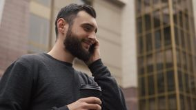 Happy beard young man talking on the smartphone and drinking coffee in the street at sunset stock footage