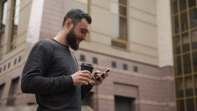 Happy beard young man texting on smartphone and drinking coffee in the street at sunset stock video footage