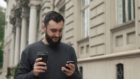 Happy beard young man texting on smartphone and drinking coffee in the street at sunset. He walks down the street stock footage