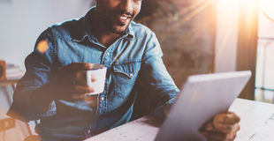 Happy bearded African man making video conversation via digital tablet with partners while working at sunny home.Concept Stock Image