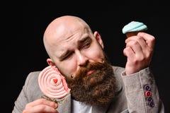 Happy bearded bald man holding two cream cakes on black background. stock photo