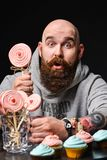 Happy bearded bald man holding two cream cakes on black background. royalty free stock photo