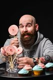 Happy bearded bald man holding two cream cakes on black background. royalty free stock images