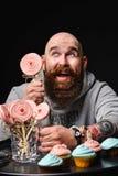 Happy bearded bald man holding two cream cakes on black background. royalty free stock image