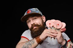 Happy bearded brutal man in a fashionable cap holds a pack of lollipops candies royalty free stock photography