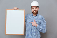 Happy bearded builder holding copyspace board and pointing. Photo of happy bearded builder holding copyspace board and pointing standing over grey background Stock Image