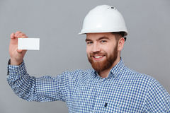 Happy bearded builder holding copyspace business card. Image of happy bearded builder holding copyspace business card standing over grey background Royalty Free Stock Image