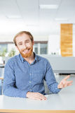 Happy bearded businessman talking and smiling in office. Happy attractive bearded young businessman talking and smiling in office Royalty Free Stock Photos