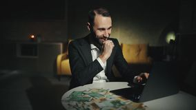 A happy bearded businessman is working at the laptop late and making a successful deal or win big money stock footage