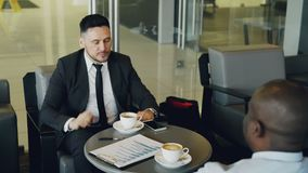 Happy bearded Caucasian businessman smiling, gesticulating, drinking coffee and discussing financial report of startup. Cheerful bearded Caucasian businessman in stock footage