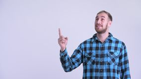 Happy bearded hipster man pointing up and looking surprised. Studio shot of bearded hipster man against white background stock footage