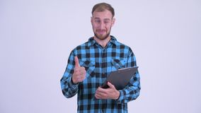 Happy bearded hipster man reading on clipboard and giving thumbs up. Studio shot of bearded hipster man against white background stock footage