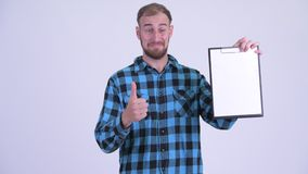 Happy bearded hipster man showing clipboard and giving thumbs up. Studio shot of bearded hipster man against white background stock video