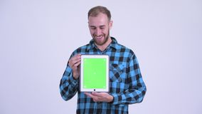 Happy bearded hipster man showing digital tablet and looking surprised. Studio shot of bearded hipster man against white background stock footage
