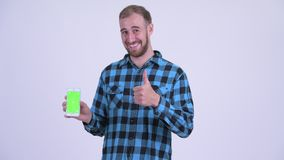 Happy bearded hipster man showing phone and giving thumbs up. Studio shot of bearded hipster man against white background stock video footage