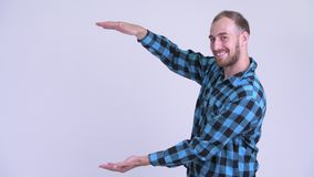 Happy bearded hipster man snapping fingers and showing something. Studio shot of bearded hipster man against white background stock video footage