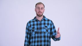 Happy bearded hipster man talking and vlogging. Studio shot of bearded hipster man against white background stock video footage