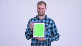 Happy bearded hipster man thinking while showing digital tablet. Studio shot of bearded hipster man against white background stock video