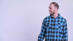 Happy bearded hipster man touching something and giving thumbs up. Studio shot of bearded hipster man against white background stock video
