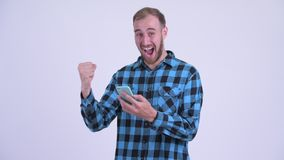 Happy bearded hipster man using phone and getting good news. Studio shot of bearded hipster man against white background stock footage