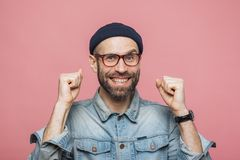 Happy bearded male with blue eyes and cheerful expression clench. Es fists, feels to be winner, demonstrates positiveness, isolated over pink background. Excited royalty free stock images