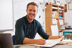 Happy bearded male teacher at desk looking to camera Royalty Free Stock Photos