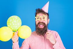 Happy bearded man in birthday cap with colourful baloons and paper star shaped glassses. Comedian with long beard and royalty free stock photography