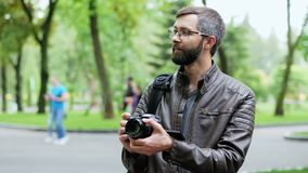 Happy bearded man with camera takes a photo in the park. Blogger takes vlog stock footage