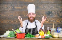Happy bearded man cooking in kitchen. Dieting with organic food. Fresh vegetables. Vitamin. man use kitchenware royalty free stock images