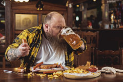 Happy bearded man drinking glass of beer Stock Image
