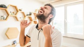 Happy bearded man gesturing with his hands celebrating win stock images