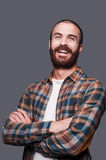 Happy bearded man. Handsome young bearded man keeping arms crossed and smiling while standing against grey background Stock Photo