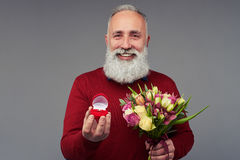 Happy bearded man holding bouquet of tulips and gift bo Royalty Free Stock Photo