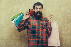 Happy bearded man holding colorful paper shopping bags. Happy bearded man, caucasian hipster, with long beard and moustache in red plaid shirt holding colorful Stock Photography