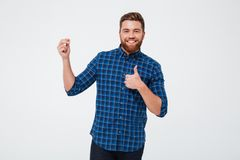 Happy bearded man holding copy space and showing thumbs up Royalty Free Stock Photography