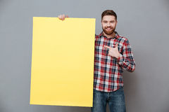 Happy bearded man holding copyspace board and pointing. Picture of happy bearded man holding copyspace board and pointing standing over grey background Stock Photo