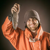 Happy Bearded Man Holding a Fresh Fish Royalty Free Stock Images