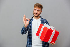 Happy bearded man holding gift box and showing ok gesture. Portrait of a happy bearded man holding gift box and showing ok gesture over gray background Royalty Free Stock Photos