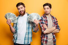 Happy bearded man holding money and looking at the camera royalty free stock image