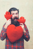 Happy bearded man holding red heart shape toy with hands. Happy bearded man, caucasian hipster, with long beard and moustache in plaid shirt holding red heart royalty free stock photo