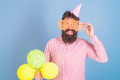 Happy bearded man in huge glasses posing with bright balloons, fun concept. Comedian with crazy look entertaining guests royalty free stock photography