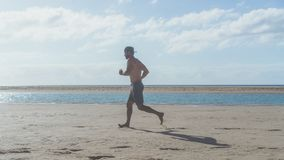 Happy bearded man jogging on the sea shore at sunrise. Side portrait of healthy young bearded man running at the beach. With bright sunlight Royalty Free Stock Image
