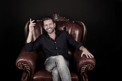 Happy bearded man in leather chair Royalty Free Stock Photography