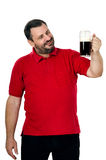 Happy bearded chap staring at porter pint. Happy bearded chap in red polo shirt staring at porter pint Royalty Free Stock Photo