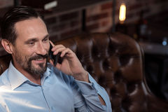 Happy bearded man listening to his interlocutor. Pleasant conversation. Positive cheerful bearded man listening to his interlocutor and laughing while having a Royalty Free Stock Images