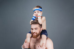 Happy bearded man with little son sitting on his shoulders. Portrait of happy handsome bearded men with his little son sitting on his shoulders over grey Royalty Free Stock Photos