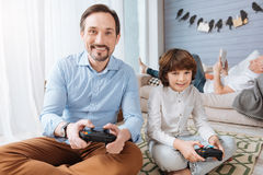 Happy bearded man playing video games with his son Royalty Free Stock Photos